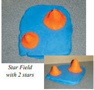 Blue clay in a flat rectangle with two orange pieces of clay in cone shapes on top.