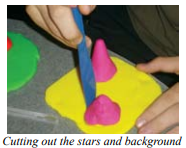A student working on clay. Yellow, flat rectangle with two gray cones of different heights.
