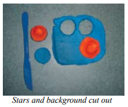 Clay cutting tool next to a rectangle of clay with two holes and one cone, the holes matching cones that have been cut out and placed on one side.